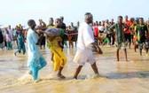 船禍發生後,人們將遇難者屍體撈上岸並送去辦理後事。(圖源:AFP)