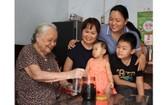 黃振英-謝珍(左一、二)母女一家四代人高興地圍著一瓶陳年鹹金桔。