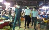 市人委會副主席楊英德(中)親往視察平田集散市場的防疫工作。(圖源:佐琳)