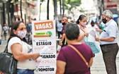 受疫情影響,全球失業率暴增。圖為巴西民眾查看職位列表公告板,一名女性將簡歷交給了招聘機構工作人員。(圖源:路透社)