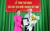 受國家主席的委託,滀臻省人委會副主席黃氏艷玉(左)向陳剛老人家轉交表彰函。