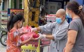 妙法寺住持釋宏心法師向貧困者贈送救濟品。