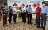 陳振松先生(左三)向第五郡第十三坊領導移交救濟物資。