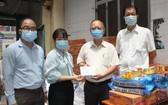穗城會館理事長盧耀南(右二)和副理事長林海泉(右一)向坊領導移交支持防疫物資和現金。