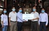 穗城會館理事長盧耀南(右二)和副理事長陳志豪(右一)向本報領導移交5000萬元贈款。