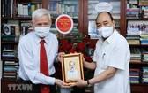 國家主席阮春福向新聞工作者鄧明芳贈送紀念品。(圖源:越通社)
