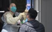 在檢測室內不用穿防護服的醫護人員為民眾採樣檢測。
