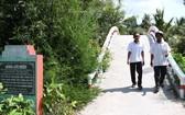 名雄(右)站在他設計和搭建的農村橋。