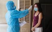 防疫工作人員為一名居家隔離者測量體溫。(圖源:VnE)