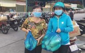 華人商販應氏蓮(左)將募集到的蔬菜送給隔離區居民。