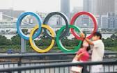 民眾與豎立在東京台場區域的奧運五環標誌合影。(圖源:新華社)