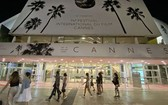 人們走過法國嘎納電影宮外的電影節海報。(圖源:互聯網)
