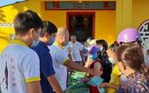 芽莊市廣東會館理事們向貧困者派發濟品。