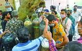 新德里居民攜氧氣鋼瓶排隊等待為居家隔離的新冠患者充醫用氧氣。(圖源:互聯網)