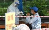 茶榮省防疫工作人員在一個檢疫點為一名過站男性進行快捷核酸檢測。(圖源:胡江)