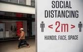 圖為英國倫敦一名男子從提示人們保持社交距離的牌子旁走過。(圖源:新華社)