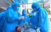 疫情防控工作人員在河內市二徵夫人郡開展防疫措施。(圖源:越通社)
