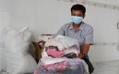 黎老師裹著贈送給清貧學生的書包、背包、衣服。