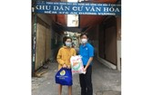 華人幹部文國寶(右)將禮物交給貧困勞動者。