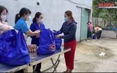 市人民議會主席阮氏麗(右二)向古芝縣受新冠肺炎疫情影響的工人與勞動者贈送禮物。(圖源:視頻截圖)