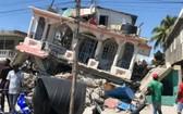 8月15日,在海地萊凱,人們站在一棟被地震損毀的房屋前。(圖源:新華社)