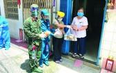 部隊與地方幹部上門派發糧食。