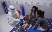 醫護人員為一名平政縣居家治療的新冠患者上門查體送藥及提供氧氣瓶。(圖源:惠春)
