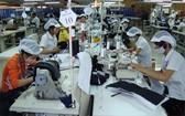 女工在成衣車間縫製服裝。(圖源:互聯網)