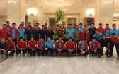 越南男子足球隊在國家主席贈送的花籃旁合影留念。(圖源:VFF)