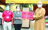 釋慧功法師向第八郡第十三坊黨委副書記馮氏貞轉交救濟品。