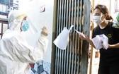 軍醫學院戰士挨家挨戶派發新冠病毒快速檢測試劑盒並指引民眾使用。