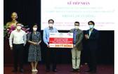 市越南祖國陣線委員會常務副主席阮成忠(左三)接收捐款與頒贈感謝狀。