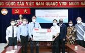 本市印尼商會和印尼人共同體代表象徵性向市越南祖國陣線委員會轉交捐贈的款項和必需品。(圖源:越通社)