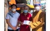 市華人佛教代表釋慧功(右一)與麒麟(左一)向啟秀華文中心校長王沛川贈送慰問金。