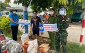 守德市勞動聯團副主席阮氏玉香(左一)向隔離區工人贈送禮物。