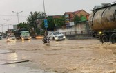 途經乂安省黃梅市的1號國道路段受淹嚴重,車輛行駛十分不便。(圖源:TTO)