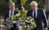 英國首相約翰遜(右)和工黨黨魁施凱爾16日前往保守黨國會議員阿梅斯遇刺身亡時的教堂,向這位同黨議員致哀。(圖源:AP)