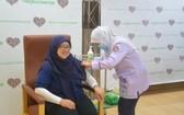 一名汶萊女性接受新冠疫苗注射。(圖源:新華社)