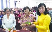 市婦聯會副主席杜氏政(右一)向民族婦女 派發紅包。