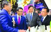 """武德膽副總理(左二)參觀越南""""魅力之城""""安江省展位展出的當地特產。"""
