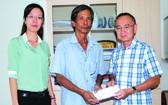 本報編委兼編輯部主任范興(右一)向畢業祥轉交5000萬元建溫情屋經費。