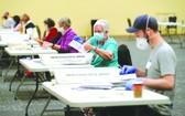 工作人員對郵寄選票進行計數。