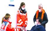 德國埃森展覽館的新冠疫苗接種中心工作人員為訪客進行登記。