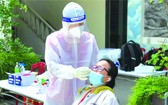 醫護人員為準備返鄉避疫大學生做採檢。