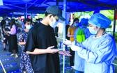 在南京市北門橋社區核酸檢測點,工作人員在用手機掃描市民身份證信息。