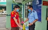 工人在上班前進行洗手消毒和測量體溫。