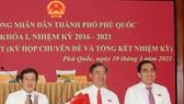 Chủ tịch HĐND TP Phú Quốc Nguyễn Đức Kỉnh (trái) và Chủ tịch UBND TP Phú Quốc Huỳnh Quang Hưng (phải) tặng hoa chúc mừng ông Đoàn Văn Tiến. ẢNH: HOÀNG DUNG