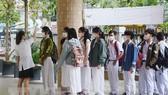 Các học sinh Trường THPT Phan Châu Trinh (thành phố Đà Nẵng) xếp hàng đo thân nhiệt trước khi vào lớp. Ảnh: TTXVN