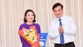 Phó Chủ tịch UBND TPHCM Lê Hòa Bình trao quyết định cho bà Bùi Thị Ngọc Hiếu. Ảnh: VIỆT DŨNG