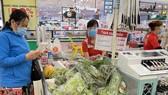 Người dân đi siêu thị đeo khẩu trang, giữ khoảng cách để phòng chống dịch. Ảnh: HOÀNG HÙNG